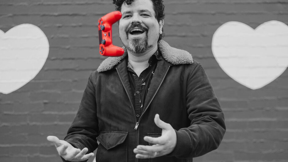 Black and white image of Eddie throwing a red PS4 controller upwards.
